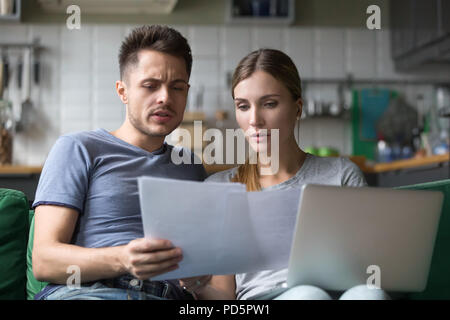 Serious confused couple checking domestic bills with papers and  - Stock Photo