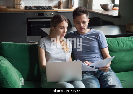 Worried couple reading documents or calculating high domestic bi - Stock Photo