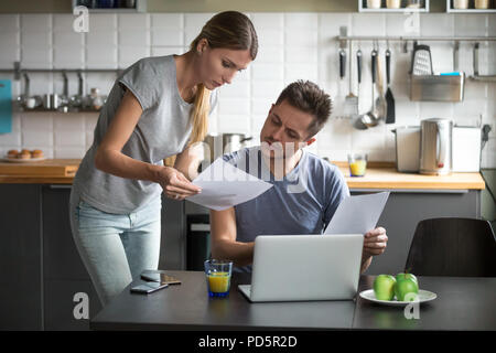 Serious young couple worried discussing utility bills in the kit - Stock Photo