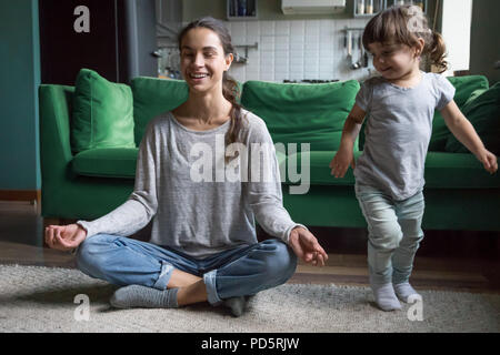 Happy mindful mother doing yoga with kid playing at home - Stock Photo
