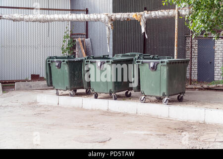Three plastic garbage cans on the street - Stock Photo