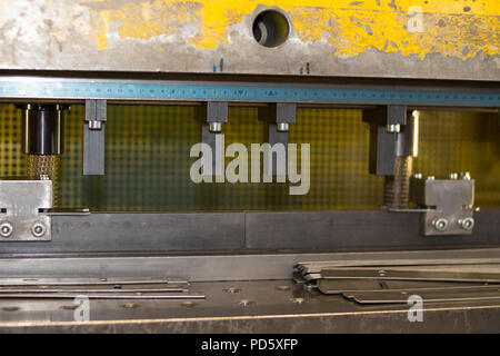 Old rustic yellow vintage retro machine part mechanical construction press for sheet metal steel processing strong press - Stock Photo