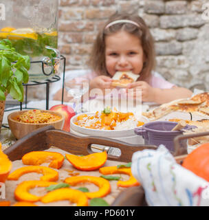 Little girl is eating pie. Family dinner in the courtyard outdoors. Autumn vegetables and fruits on the table. Dining table . A special place for text. - Stock Photo