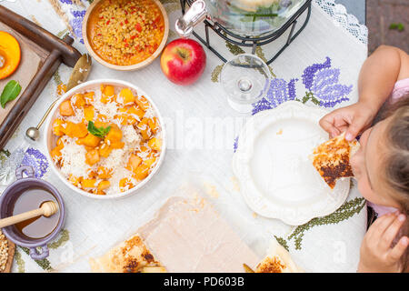 Little girl is eating pie. Family dinner in the courtyard outdoors. Autumn vegetables and fruits on the table. Dining table top view. A special place for text. - Stock Photo