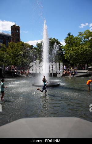 Little girl cools down running through Washington Square Park fountain during summer heat wave in West Village, Manhattan on August 28th, 2014, Manhat - Stock Photo