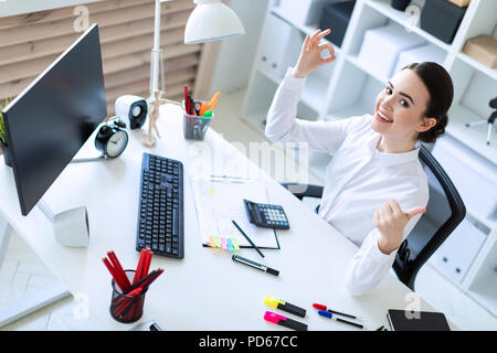 A young girl in the office sits at a table, works with documents and shows a sign of okay and class. - Stock Photo