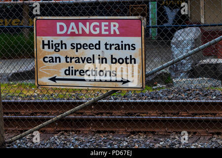 Worn aged dirty danger high speed trains can travel in both directions sign - Stock Photo