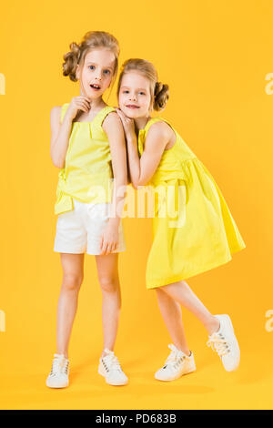 The girls of the twins stand together on a yellow background. - Stock Photo