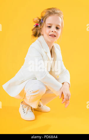 A teenage girl in white clothes is squatting on a yellow background. - Stock Photo