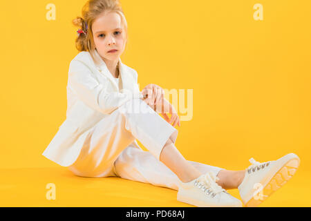 A teenage girl in white clothes sits stretching her legs forward on a yellow background. - Stock Photo