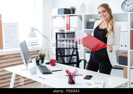 A young girl stands in the office near the table and holds a folder with documents in her hands. - Stock Photo