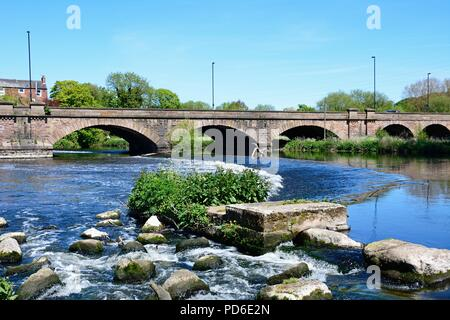 View across boulders and the weir towards the Trent Bridge road bridge A511 over the River Trent, Burton upon Trent, Staffordshire, England, UK, Weste - Stock Photo