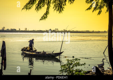 A fisherman readies his net on his boat as a dock wades around on shore. Cam Kim Island on the river bank. Hoi An VN - Stock Photo