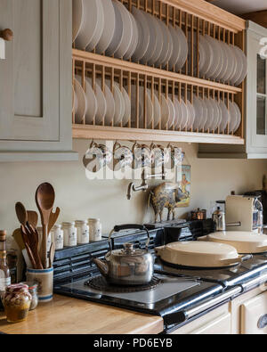 Wooden plate rack above AGA with kettle on hob - Stock Photo