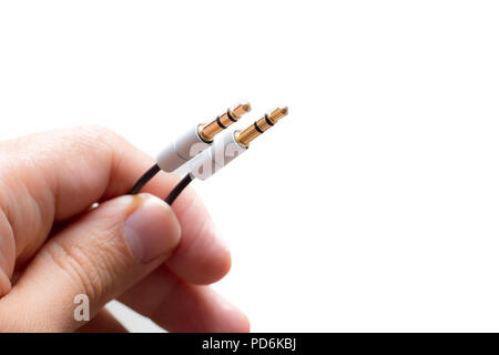 Hand with two stereo audio cable gold coated isolated on white backgrounds - Stock Photo