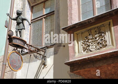 INNSBRUCK, AUSTRIA - JULY 2, 2018: Close-up on a hanging commercial sign with a small girl figurine, located in the historic center on street Hofgasse - Stock Photo