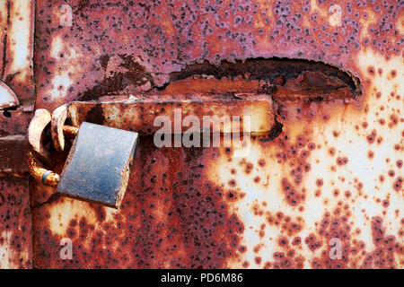 Rusty old lock on red grungy background, textplace - Stock Photo