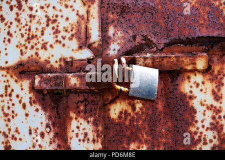 old rusted lock on a white and brown rusty gate. Rusty old lock on red background, place for text. - Stock Photo