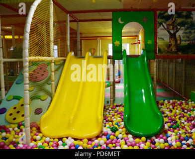 Yellow and green baby slides going down to the pool with many colored balls in the kids playing room. - Stock Photo