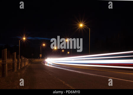 Streetlights light trails from cars and traffic on highway at night on a busy road street - Stock Photo