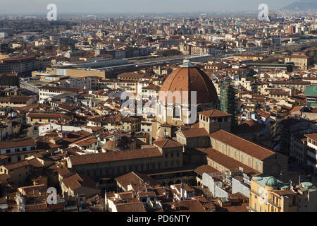 Basilica di San Lorenzo (Basilica of St Lawrence) and the dome of the Cappella dei Principi (Chapel of the Princes) rising over the tiled roofs of the Florence downtown pictured from the dome of the Florence Cathedral (Duomo di Firenze) in Florence, Tuscany, Italy. Santa Maria Novella railway station is seen in the background. The Laurentian Library (Biblioteca Medicea Laurenziana) is seen in the foreground left from the dome and the basilica. - Stock Photo
