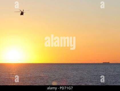 An MH-60R Seahawk helicopter assigned to Helicopter Maritime Strike Squadron (HSM) 70 and the aircraft carrier USS George H.W. Bush (CVN 77) flies over the Atlantic Ocean at sunrise Oct. 17, 2010. George H.W. Bush is conducting tailored ship's training availability/final evaluation problem. (U.S. Navy photo by Mass Communication Specialist 3rd Class Tony Curtis/Released) - Stock Photo