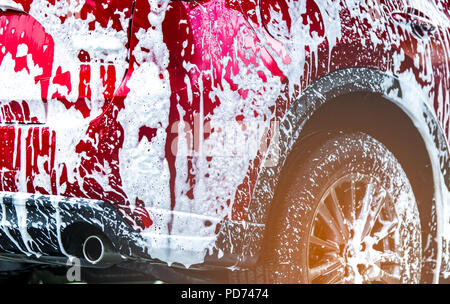 Red compact SUV car with sport and modern design washing with soap. Car covered with white foam. Car care service business concept. Car wash with foam - Stock Photo