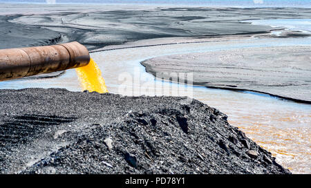 The industrial wastewater is discharged from the pipe into the water - Stock Photo
