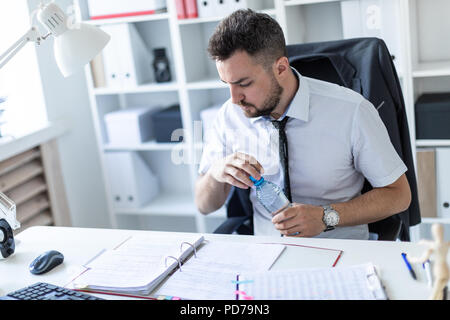 A man is sitting at a table in the office, working with documents and opening a bottle of water. - Stock Photo