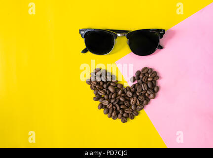 top view flat layer funny face made from coffee beans in smile  icon shape , and sun glasses on two tone multicolored  background - Stock Photo