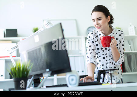 A young girl is standing in the office near the table, holding a red mug in her hand and typing on the keyboard. - Stock Photo