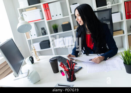 Beautiful young girl fills the documents, sitting in the office at the table. - Stock Photo