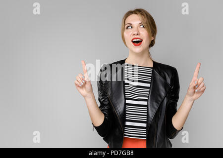 A young girl in a leather jacket shows on her hands index fingers. Portrait of a girl with blond hair in a leather jacket - Stock Photo