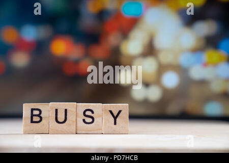 busy word Written In Wooden Cube on wood table with traffic bokeh in background - Stock Photo