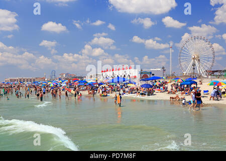 People enjoy the beach along the coastline in Ocean City, New Jersey, USA - Stock Photo