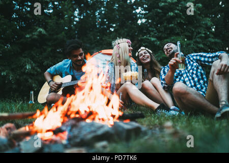 Cheerful young friends having fun by campfire - Stock Photo