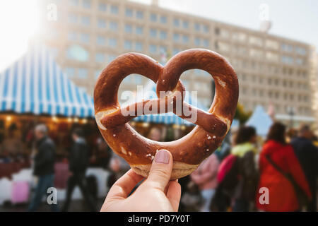 A girl or a young woman is holding a traditional German pretzel in the street. Oktoberfest festival in the background. - Stock Photo