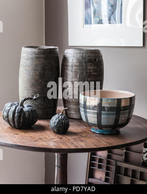 Two wooden pots from South Africa are displayed on a small table in the living room with dried gourds and a bowl from Anta.