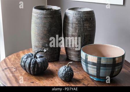 Two wooden pots from South Africa are displayed on a small table in the living room with dried gourds and a bowl from Anta. - Stock Photo
