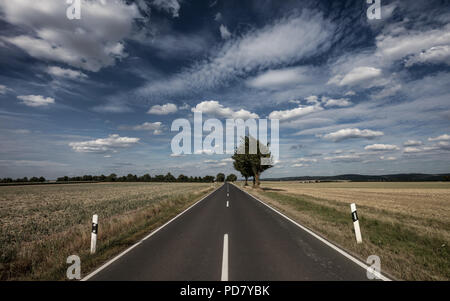 Endless country road in Germany - Stock Photo