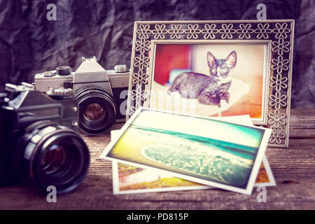 Old photographic camers with vintage prints and photo frame on wooden desk - Stock Photo