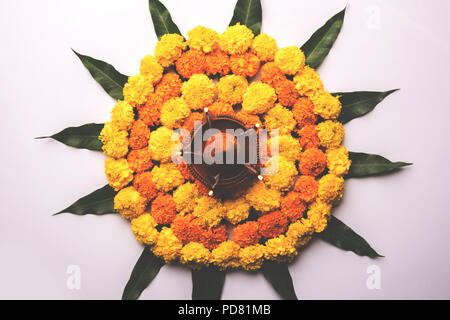 Flower Rangoli for Diwali or Pongal Festival made using Marigold or Zendu flowers and mango leaf and Clay Oil Lamp over white background, selective fo