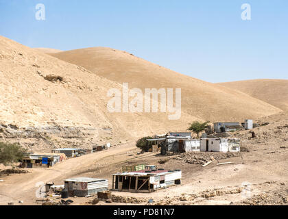 Small Bedouin Arab settlement in arid desert conditions on the West Bank next to the Jerusalem to Dead Sea Road - Stock Photo