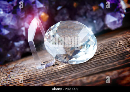 Clear colorless rhinestones on wooden board with amethyst geode in background - Stock Photo