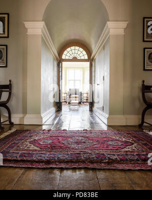 Antique rug in hall leading through to dining room with double doors - Stock Photo