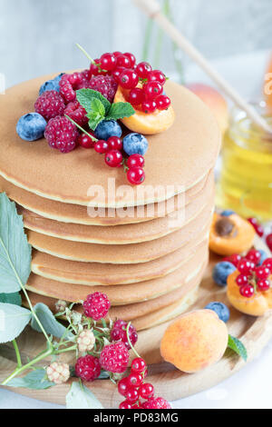 Fresh delicious pancakes with summer raspberries, blueberries, red currants, apricot, peach and mint. Pink phlox bouquet, two glasses of orange juice, - Stock Photo