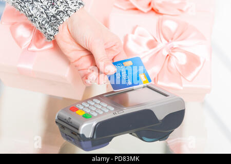 Hand holding contactless credit or debit card over wireless payment terminal at shop with gifts in the background - Stock Photo
