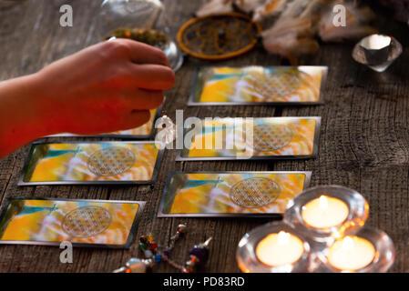 Fortune teller holding a pendulum over tarot cards - Stock Photo