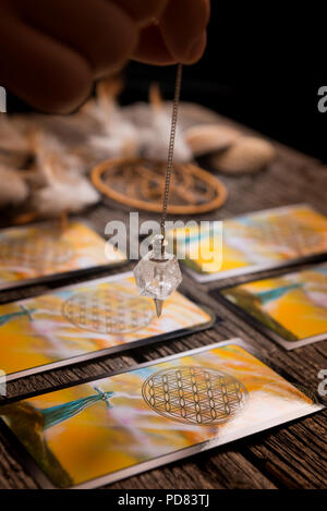 Fortune teller holding a pendulum over tarot cards - Stock Photo