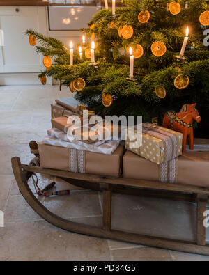 Wrapped presents on a wooden sledge underneath candle lit christmas tree - Stock Photo